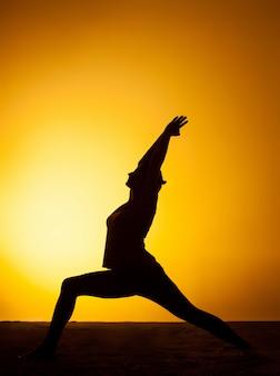 La mujer practicando yoga en la luz del atardecer