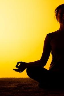 Mujer practicando yoga en la luz del atardecer