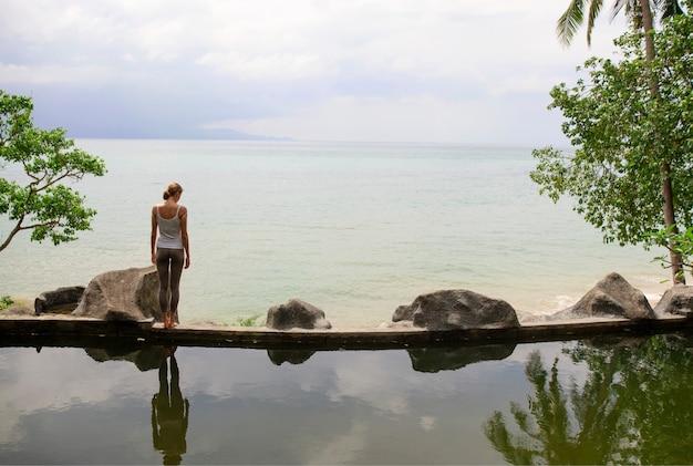 Mujer practicando yoga de meditación matutina en la playa.