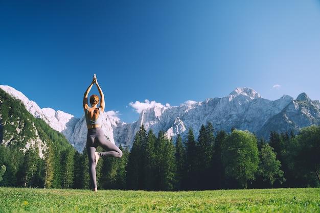 Mujer practicando yoga en la naturaleza mujer joven haciendo yoga en las montañas