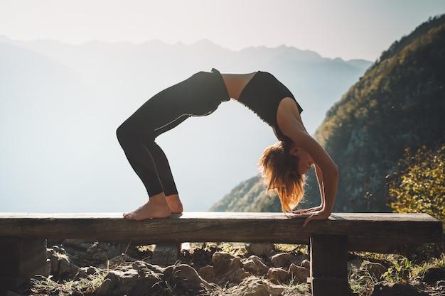 Mujer practicando yoga en la naturaleza mujer joven está meditando sobre fondo de montañas
