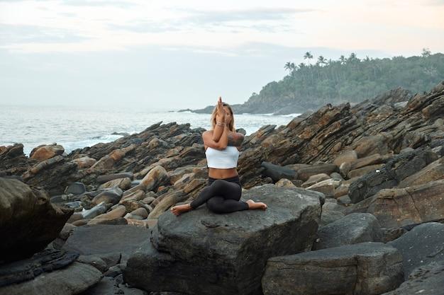 Mujer practicando yoga en la naturaleza