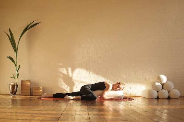 Mujer practicando yoga restaurativo en un hermoso estudio