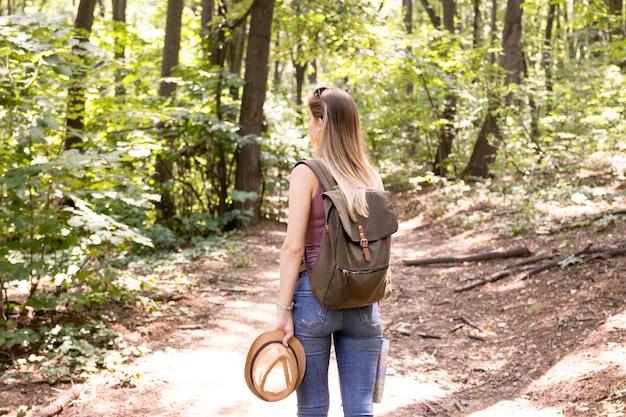 Mujer preguntando en el bosque por detrás
