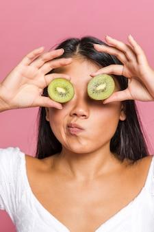 Mujer preguntándose y cubriéndose los ojos con kiwi