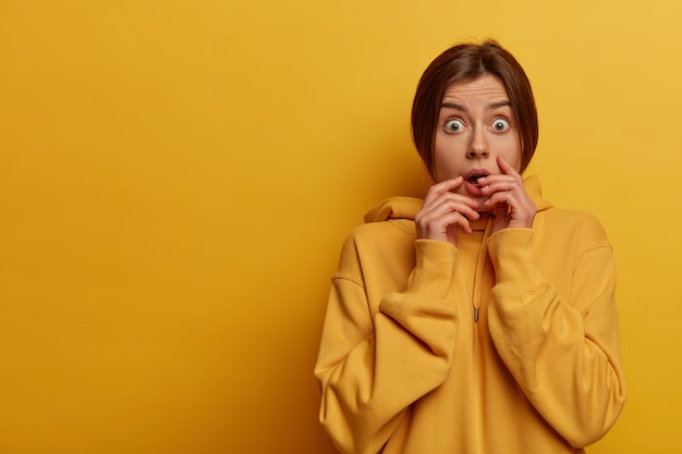 Mujer preocupada ansiosa asustada emocionalmente mira con gran miedo a la cámara, no puede creer lo que ve, contiene la respiración, usa sudadera amarilla