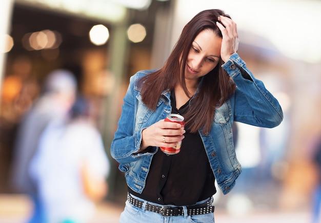 Mujer preocupada con una lata en la mano