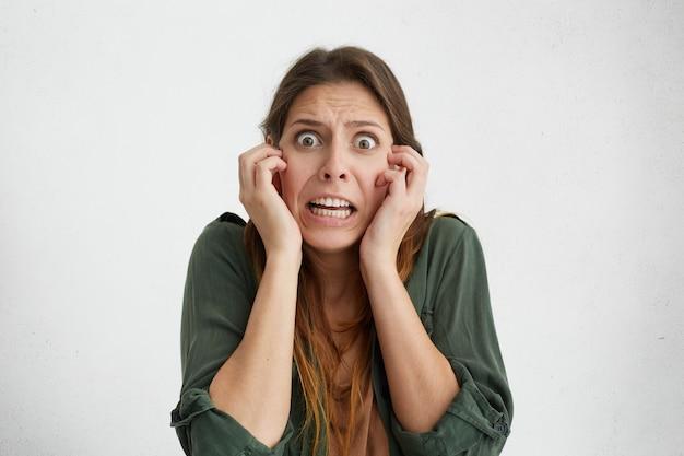Mujer preocupada con ojos oscuros saltones manteniendo las manos en las mejillas mirando desesperadamente asustada por algo horrible.