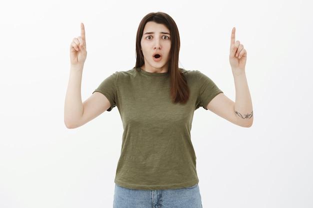 Mujer preocupada preocupada y nerviosa sorprendida que reacciona a noticias desagradables e inquietantes jadeando con la boca abierta de sorpresa apuntando hacia arriba con las manos levantadas en el lugar del accidente, posando sobre una pared gris