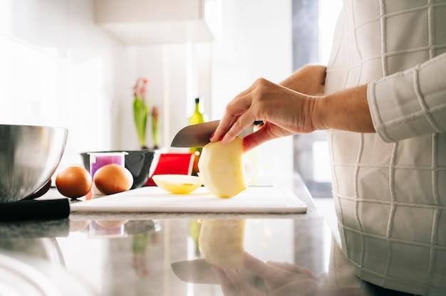 Una mujer prepara los ingredientes para hacer un bizcocho en la cocina de su casa.