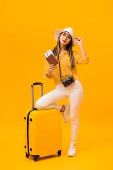Mujer preparada para vacaciones con equipaje y elementos esenciales de viaje