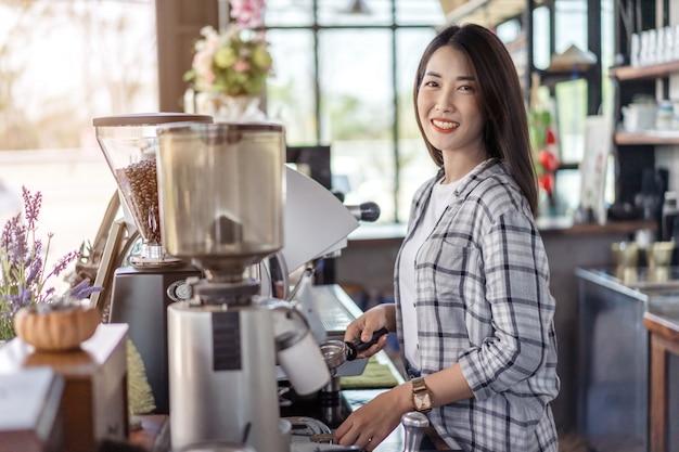 Mujer preparando café con máquina en café