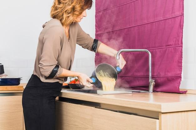 Mujer preparando espagueti hervido