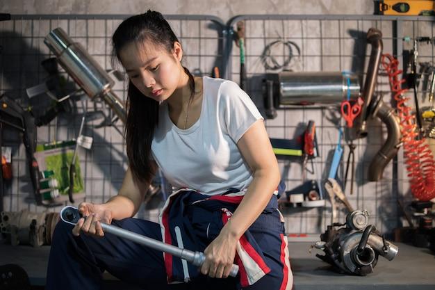 Mujer preparando la llave para trabajar en el garaje