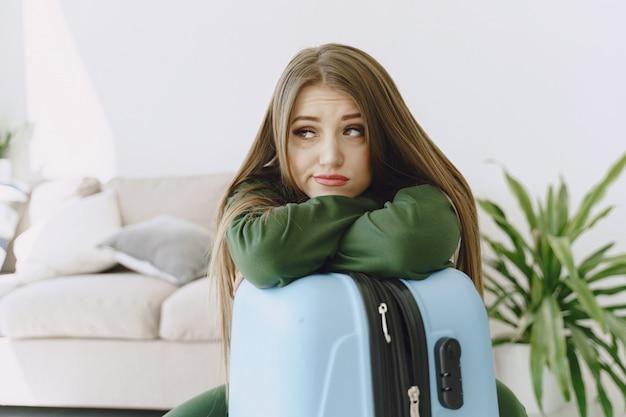 Mujer preparando maleta de viaje en casa