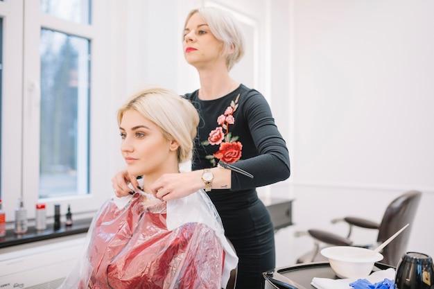 Mujer preparando a niña para el tratamiento del cabello