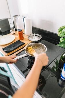 Mujer preparando pasta de rigatoni en una cacerola