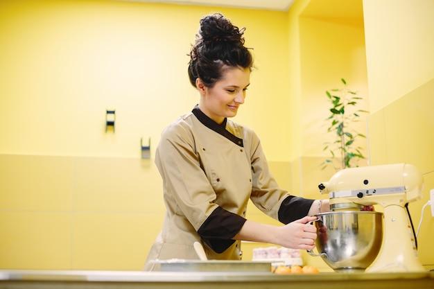 Mujer preparando pasteles. pastelero con abrigo.