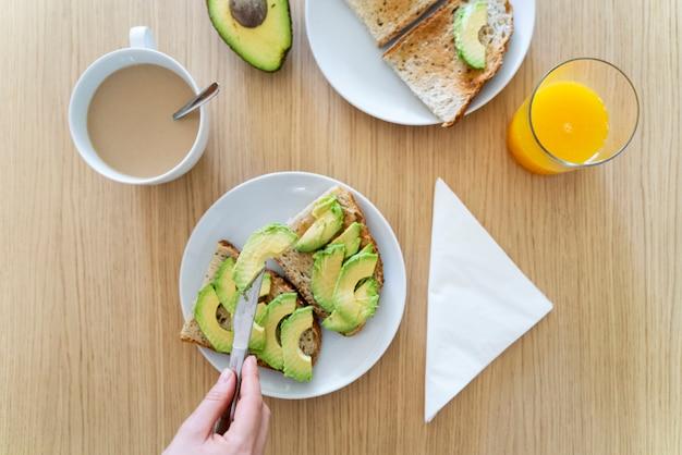 Mujer preparando tostadas de aguacate fresco. vista superior de las manos sosteniendo un cuchillo de cocina en el desayuno.