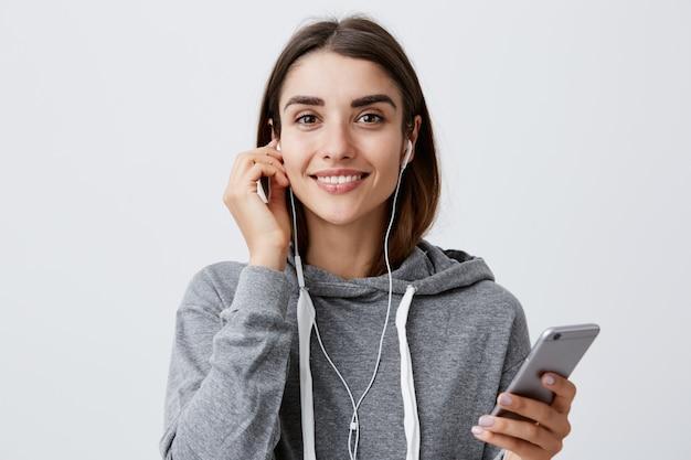 Mujer preparándose para caminar en el parque. concepto de estilo de vida urbano. chica joven y bella morena estudiante caucásico en gris con capucha sonriendo con dientes, con los auriculares puestos, con smartphone en las manos.