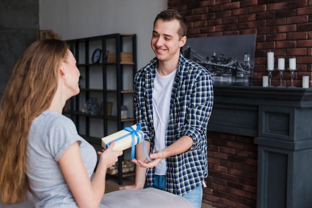 Mujer presentando regalo al hombre en casa.