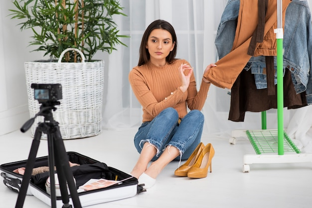 Mujer presentando ropa nueva en cámara