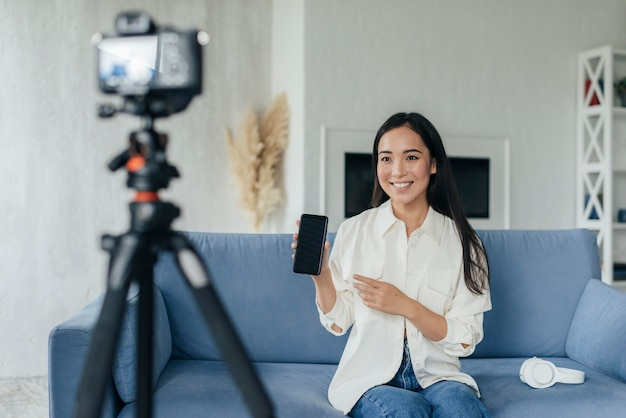 Mujer presentando su teléfono en una transmisión en vivo