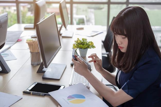 La mujer presiona la calculadora en el escritorio.