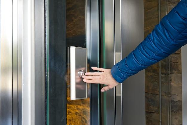 Mujer presionando el botón del ascensor moderno de vidrio.