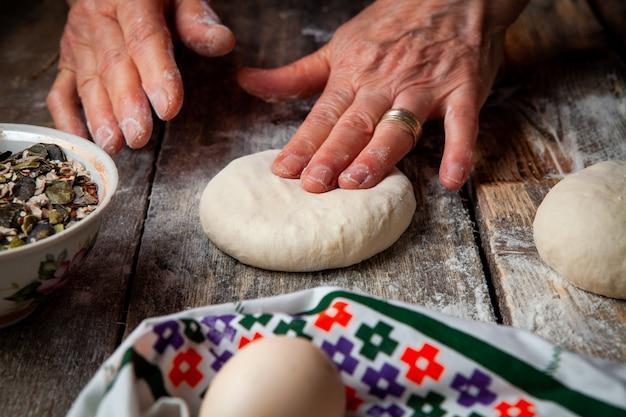 Mujer presionando la masa con las manos en primer plano de la mesa de madera.