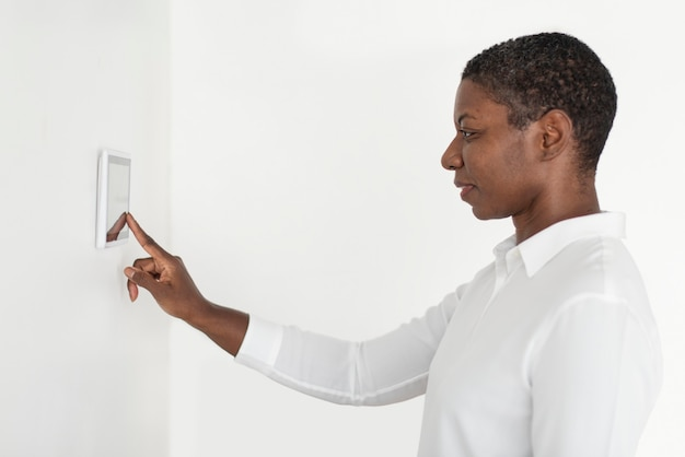 Mujer presionando sobre el monitor del panel de automatización del hogar inteligente