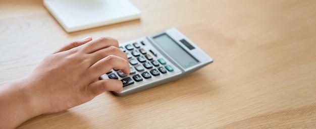 Mujer presione calculadora para calcular los gastos de ingresos y planes para gastar dinero en la oficina en casa.