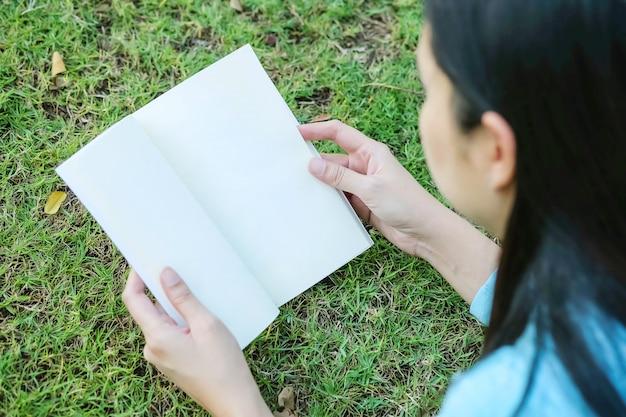 La mujer del primer mintió en el piso de la hierba para leer un libro en tiempo libre en el jardín