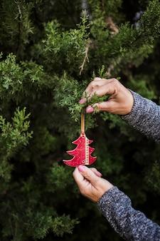 Mujer de primer plano con adornos navideños en forma de árbol