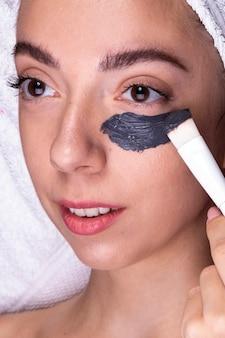 Mujer de primer plano aplicando producto para el cuidado de la piel