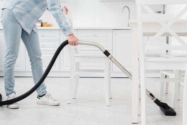 Mujer de primer plano con aspiradora para limpiar