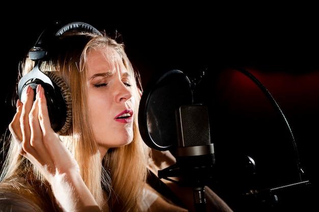 Mujer de primer plano con auriculares cantando
