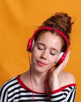 Mujer de primer plano con auriculares y fondo naranja