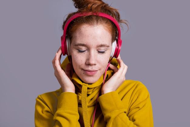Mujer de primer plano con auriculares rojos y sudadera con capucha amarilla