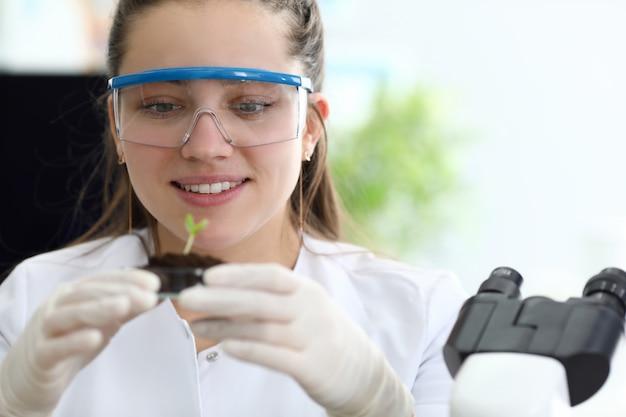 Una mujer en primer plano, una bióloga científica en un laboratorio de investigación, examina las propiedades biotecnológicas de las plantas. pruebas médicas y bioquímica.