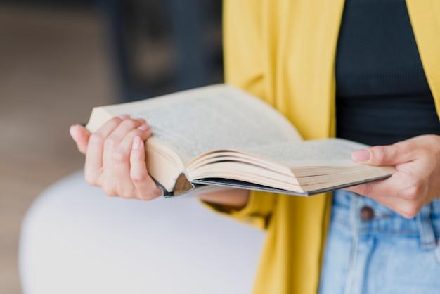 Mujer de primer plano con blusa amarilla y libro