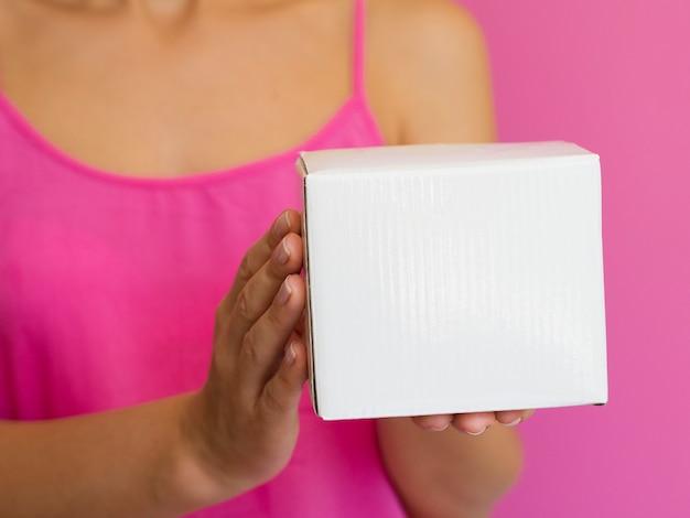 Mujer de primer plano con camisa rosa y caja