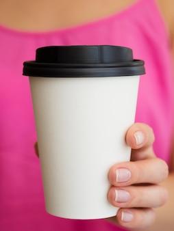 Mujer de primer plano con camisa rosa y taza de café