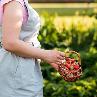 Mujer de primer plano con cesta de frutas