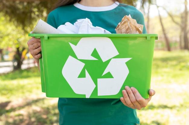 Mujer de primer plano con cesta de reciclaje en la naturaleza