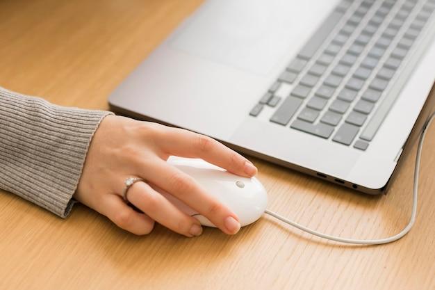 Mujer de primer plano en la computadora portátil con mouse