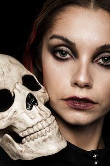 Mujer de primer plano con cráneo humano