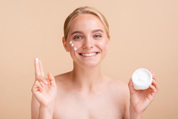 Mujer de primer plano con crema para la cara y tarro