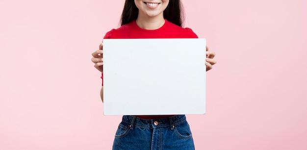 Mujer de primer plano con hoja de papel en blanco