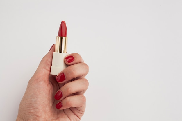Mujer de primer plano con lápiz labial rojo y fondo blanco.